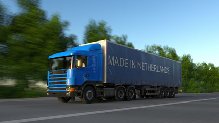 Speeding freight semi truck with MADE IN NETHERLANDS caption on the trailer. Road cargo transportation. 3D rendering