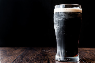 Dark Beer on wooden surface.