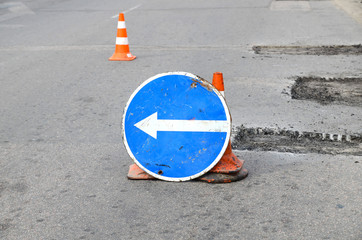 Road repairs. Plastic orange cone on the asphalt road. Detour sign on the street, roadworks. Restricted local government budgets are reflected in potholes and damaged roads.