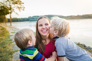 Mother with two sons at the lake, sunny spring day.