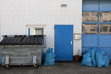 Hinterhofgarage mit blauer tür und blauem Tor , davor steht ein Müllcontainer