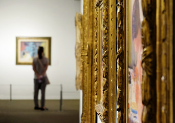 Girl looks at a painting at the Museum of Art
