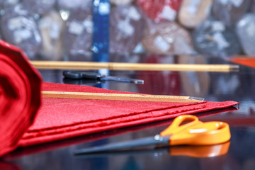 roll of red material lying on the cutting table in the Studio on tailoring of textiles