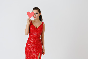 Beautiful long-haired brunette in a red dress holding a red heart. Studio, white background