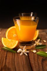 Orange juice in cup of glass with blossom, fresh fruits on wooden background