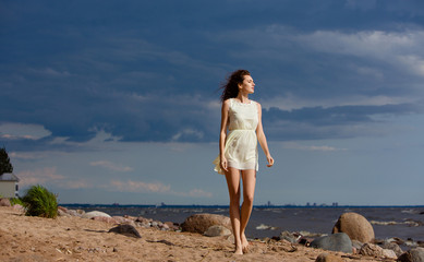 Beautiful slim barefoot girl walking on a beach against the sea