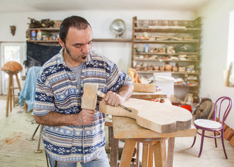 artist processing wood with a chisel in the studio
