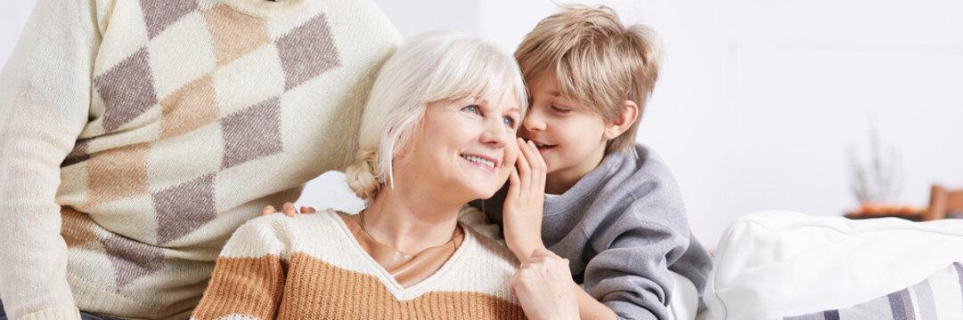 Boy whispering to grandma's ear