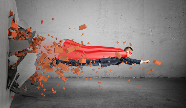A superhero businessman in a cape flying right through the wall leaving rubble behind him.