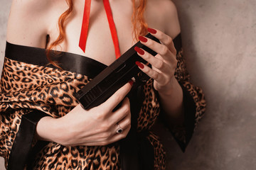 A woman with red hair in leopard print gown with a gun in his hand. Red-haired girl with pale skin and blue eyes with a bright unusual appearance with a red ribbon around her neck. French courtesan