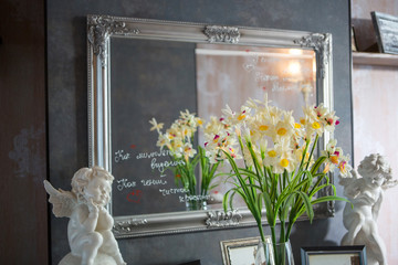 Paintings on the dresser in front of the mirror French style. Photos are taken by mirror. Romantic interior. Angels