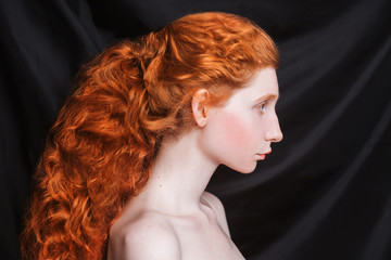 Woman with long curly red hair gathered in ponytail on black background. Red-haired girl with pale skin, blue eyes, unusual appearance without makeup. Natural beauty. Girl from the era of renaissance