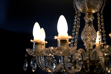 Chandelier of crystal with burning lights on a dark background
