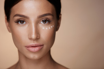 Beauty Cosmetics. Closeup Of Woman With Concealer Under Eyes