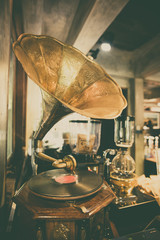 Retro gramophone with horn speaker for playing music over plates.