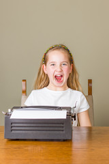 Young girl angry and screaming while working on old typewriter
