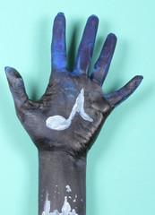ладонь синего цвета на ней нарисована музыкальная нота