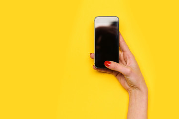 girl touch mobile phone screen with hand on yellow background