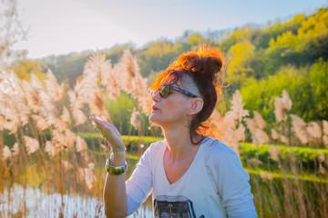 Femme devant les roseaux en contre-jour au bord de l'étang