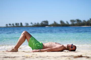Homme au maillot vert fluo bronsant sur la plage de Nassau, Bahamas