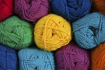 Symmetrically positioned rainbow colored cotton yarns background.