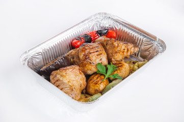 Close up Healthy restaurant food delivery in foil box. Grilled meat steak and vegetables. Meals take away, selective focus. Isolated on the white background.