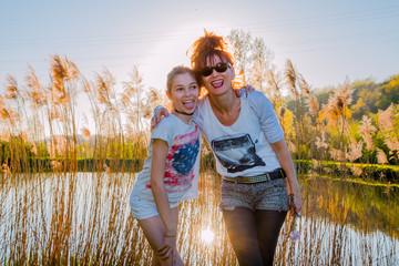 Fillette et femme devant les roseaux en contre-jour au bord de l'étang