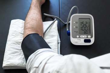 Hypertensive patient performing a blood pressure auto test / man self-monitoring of blood pressure with a tensiometer