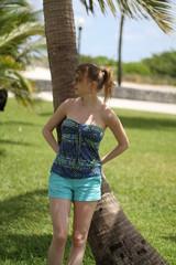 Femme à queue de cheval devant un palmier