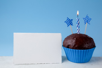 Birthday concept with cupcake and candle next to empty greeting card on blue background