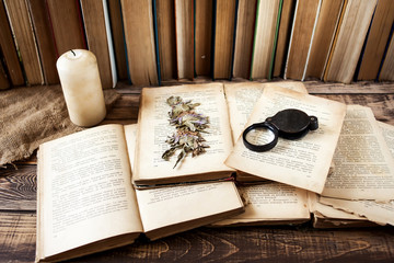 Old books with pen on the wooden table, white candle, many books on background