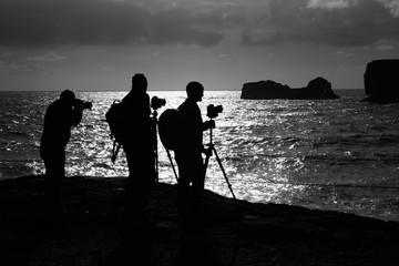 Photographers taking pictures on famous Reynisdrangar rock formations in Iceland