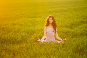 Young woman doing complex Yoga exercise on green lawn at sunset
