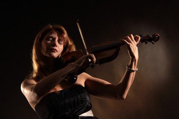sensual woman playing violin with passion