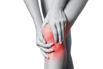 Closeup view of a young woman with knee pain. isolated on white background. Black and white photo with red dot.