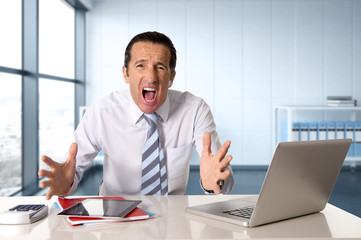 stressed senior businessman with tie in crisis working on computer laptop at desk in stress under pressure