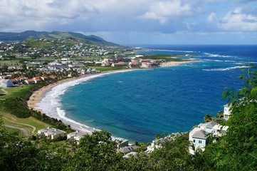 A view over St. Kitts Island with residential area and beaces on the foreground and lush green hills on the background