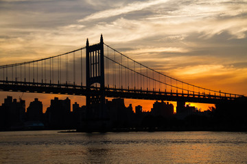 Triborough bridge and city with cloudy sunset sky, New York