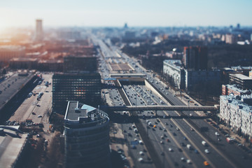True tilt shift shooting of highway in metropolis from high point: multiple residential and office buildings, parking, many cars on busy streets of the city, crosstown traffic, sunny springtime