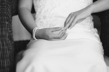 Foto b/n delle mani di una sposa che si tiene il dito in segno di impazienza