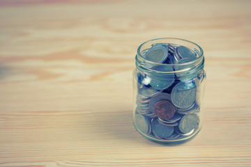 Money and banking concept with coins and glass Jar for savings on wooden background with filter effect retro vintage style