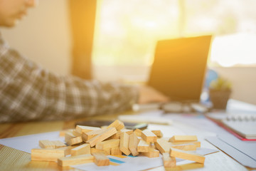 man is playing jenga,a wood blocks tower game for practicing mental skill with business,Exhausted businessman falling asleep at his office desk,entrepreneur background,selective focus,vintage color