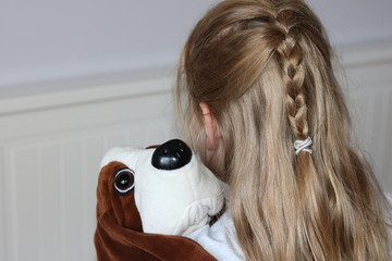 Lonely blond hair girl with plush dog in arms