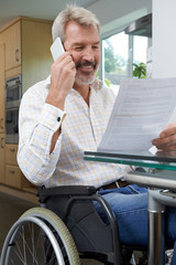 Man In Wheelchair Making Phone Call Whilst Reading Letter