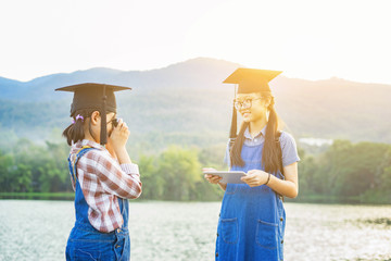 Two young girls graduate being photograph in a park with a DSLR mirrorless camera,happy international students in boards and bachelor gowns taking photo with smartphone ,morning light,vintage color.