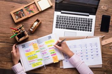 Businesswoman Writing Schedule In Calendar Diary