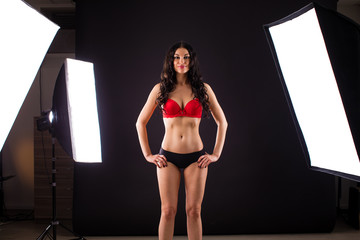Conditions of work in the studio, a professional model in red and black uderwear posing in photo studio