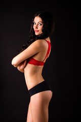Portrait of sexy brunette woman in red and black underwear on a dark wall