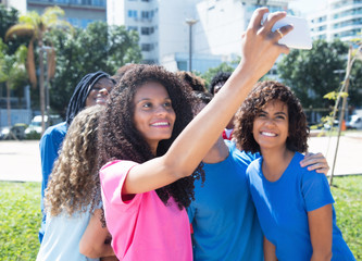 Large group of laughing man and woman taking selfie