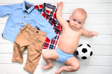 Baby on white wooden background with clothing  and football toy. Wish list or shopping overview for pregnancy and baby shower